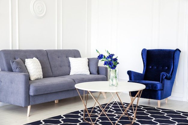 Modern living room interior - navy blue corduroy armchair, sofa with cushions, round table and vase with a bouquet of blue flowers.