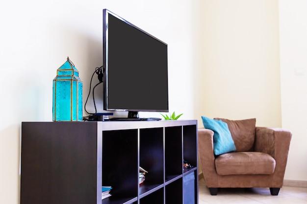 Современный интерьер гостиной, умный телевизор, велюровое кресло, подушки. полка, арабский фонарь. макет. концепт дизайна.