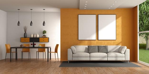 Современная гостиная с диваном у оранжевой стены и обеденным столом со стульями