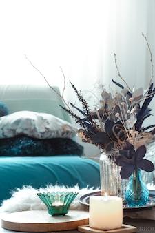 Современная гостиная с искусственными цветами в вазе и предметами домашнего декора на деревянном светлом столе.