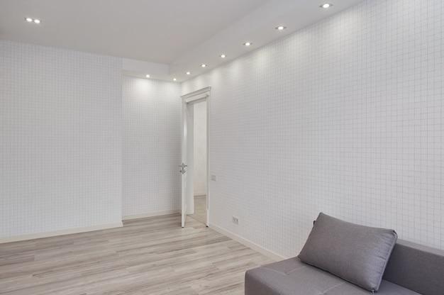 Современная гостиная с большой пустой белой стеной и серым диваном, без людей