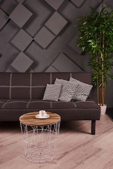 Modern living room with brown sofa, coffee table, pot plant and grey wall