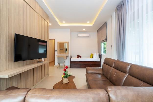 Современная гостиная с коричневым диваном, телевизором и кушеткой