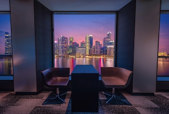 Modern living room with view Singapore skyline at night.