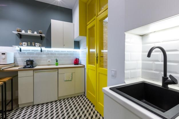 黄色の内部ドアを備えたモダンなロフトスタイルのキッチン