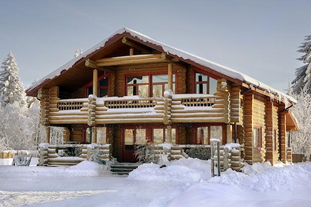 Современный бревенчатый домик, деревянный загородный дом, зимний бревенчатый дом с большими окнами, балконом и верандой.