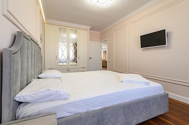 Современный роскошный интерьер спальни с двуспальной кроватью в бежевых и коричневых тонах