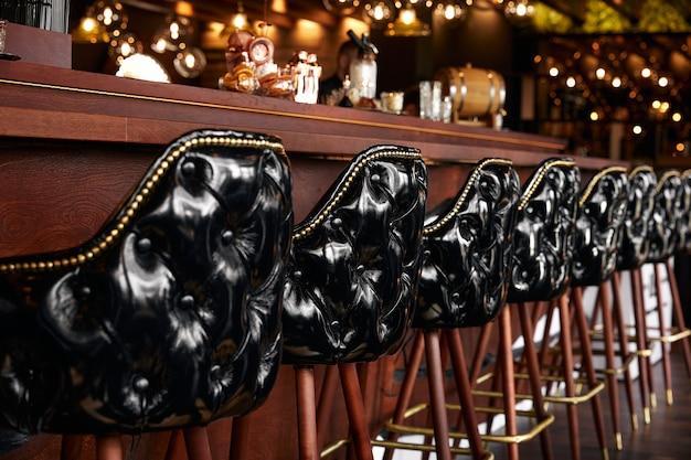 Современный роскошный интерьер в черном стиле с черными кожаными креслами