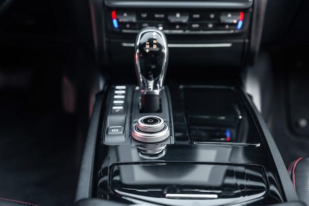 Интерьер современного роскошного автомобиля. панель управления, магнитола, рычаг переключения передач. рычаг переключения передач акпп. выборочный фокус.