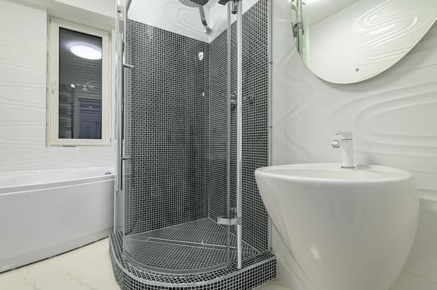 洗面台、楕円形の鏡、ウォークインシャワーキャビンを備えたモダンで豪華な白とクロムのバスルーム