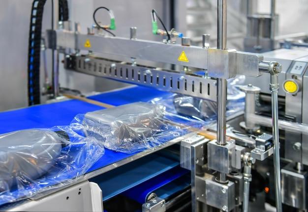 Современная машина для упаковки продуктов на конвейерной ленте на заводе