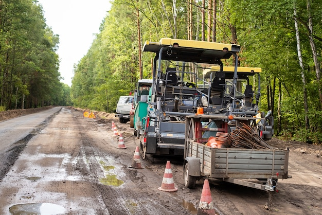 Modern machines for constructing asphalt roads on the sideroad. pause in construction new roads because of rainy bad weather