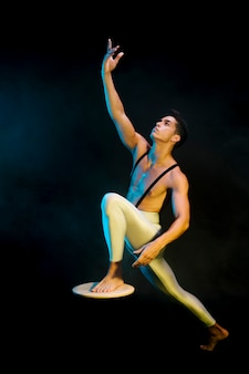 Modern male ballet performer dancing in spotlight