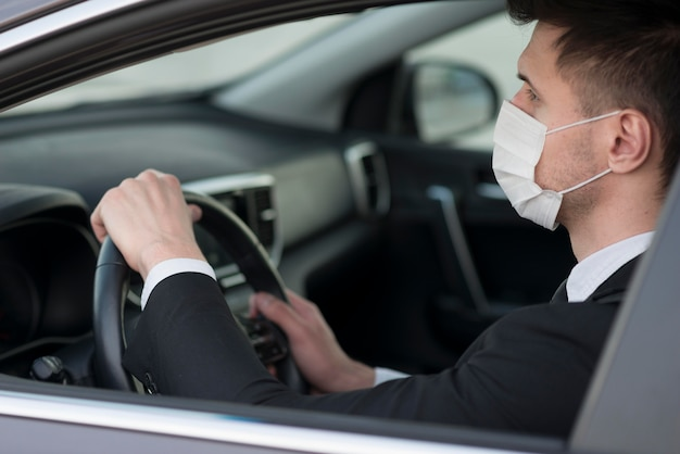 Modern man in car with mask