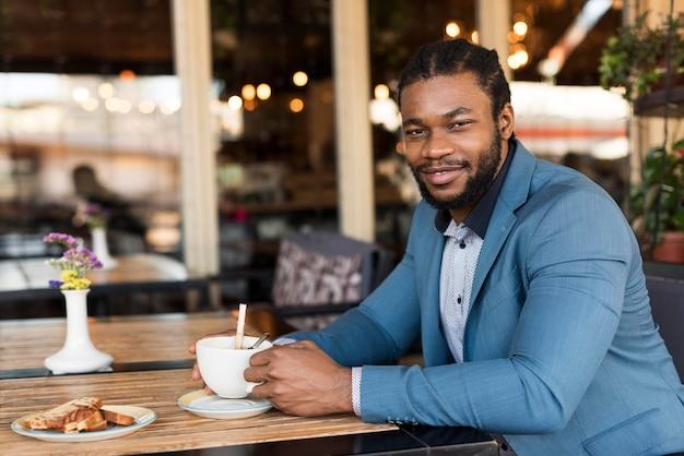 Modern man drinking his coffee in a restaurant