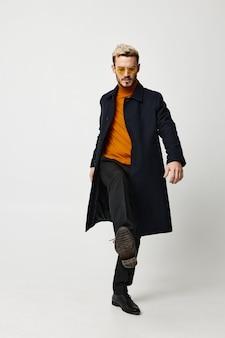 暗いコートを着た現代人と、ライトにフルレングスのズボン、顔にメガネ