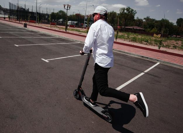街で電動スクーターに乗ってスタイリッシュな黒と白の衣装で現代人。