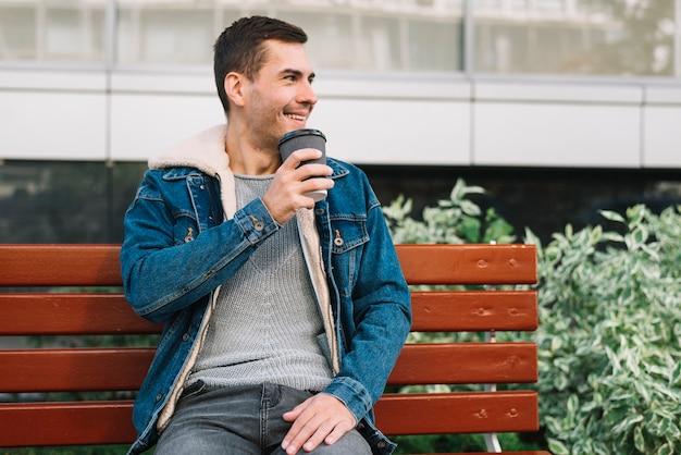 Modern man sitting on bench in urban environment