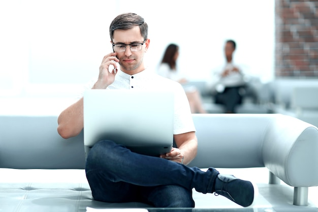 Современный человек сидит в вестибюле современного отеля