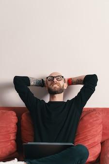 頭の後ろに手でリラックスできるラップトップでソファに座っている現代人