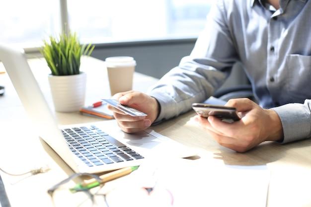 온라인 결제를 위해 신용카드와 휴대전화를 사용하는 현대인. 모바일 쇼핑 개념입니다.