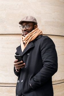 屋外で彼の電話を使用している現代人