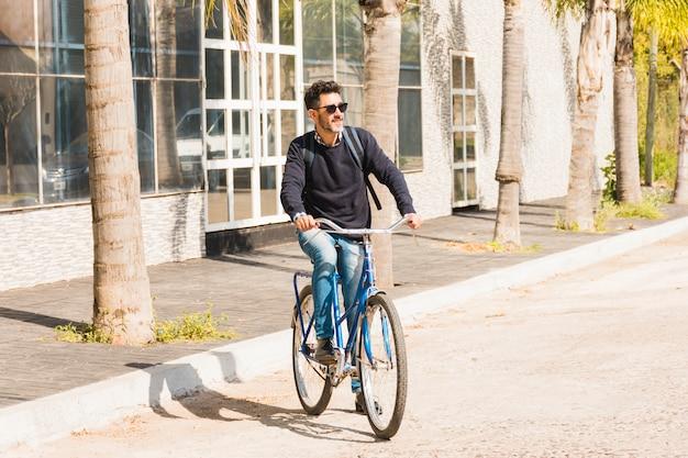 Современный человек в темных очках катается на велосипеде по улице