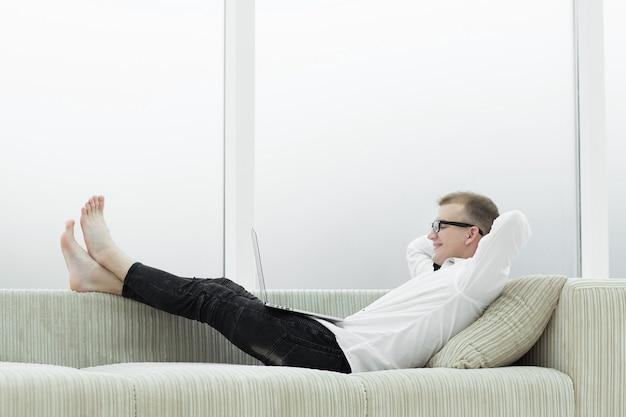 거실에서 소파에 누워 노트북과 현대인