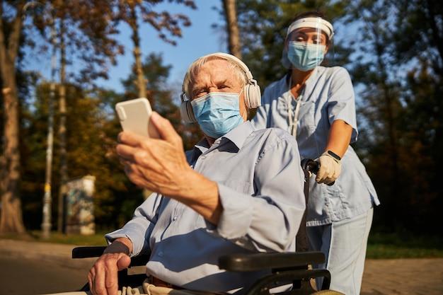 야외에서 좋은 날씨를 즐기는 휴대폰과 헤드폰을 가진 현대인