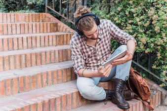 Modern man with tablet on stairs