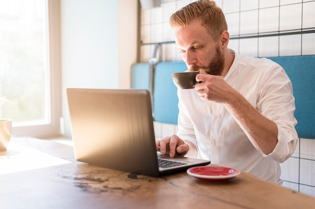 Modern man working on his laptop while drinking coffee