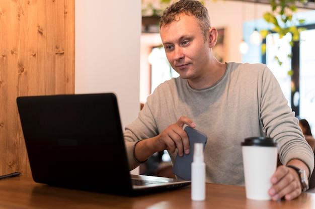 一杯のコーヒーを保持しながら働く現代人