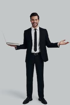 現代のマネージャー。カメラを見て、灰色の背景に立っている間ラップトップを保持している完全なスーツのハンサムな若い男の全長