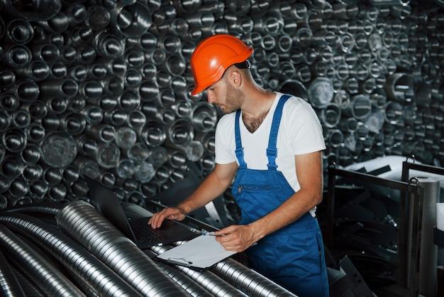 Современное производство. мужчина в военной форме работает на производстве. современные промышленные технологии.