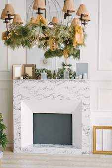 Modern marble fireplace in the living room or dining room, decorated for christmas
