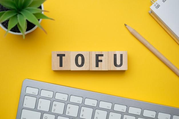 Современное маркетинговое модное слово tofu top of funne. вид сверху на деревянный стол с блоками. вид сверху.