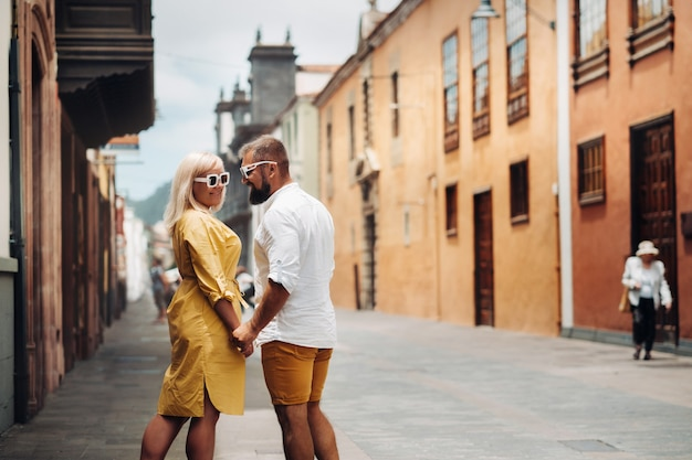 A modern married couple of lovers strolling in the old town of the island of tenerife, a couple of lovers in the city of la laguna.
