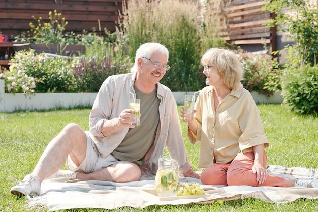 裏庭の芝生に座って新鮮な自家製レモネードを飲み、何かについて話している現代の既婚高齢者