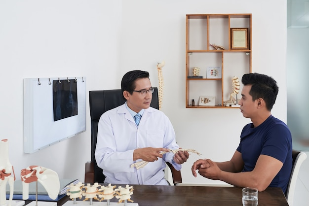 손목 외상을 가진 환자에게 상담하는 팔 골격 모델을 들고 책상에 앉아 있는 현대의 성숙한 아시아 정형외과
