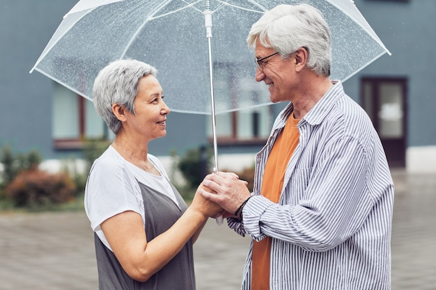 Современная зрелая пара под зонтиком