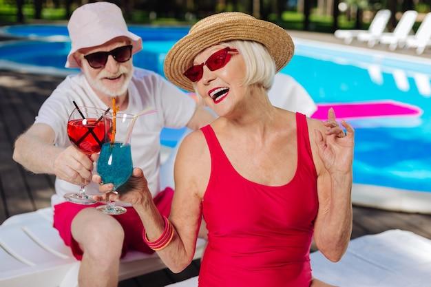 Современные зрелые мужчина и женщина в яркой одежде пьют освежающие коктейли
