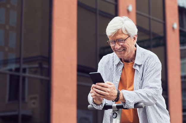 Современный зрелый мужчина текстовых сообщений на открытом воздухе