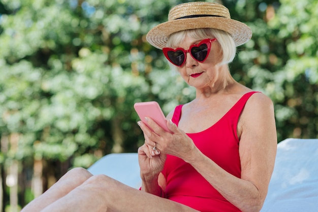 Modern mature woman wearing stylish straw hat holding her pink smart phone in hands