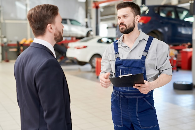 Modern mechanic talking to client