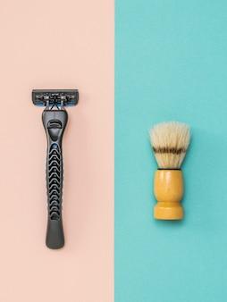 Современная мужская бритва и кисточка для бритья на двухцветном фоне. набор для ухода за мужским лицом. плоская планировка.