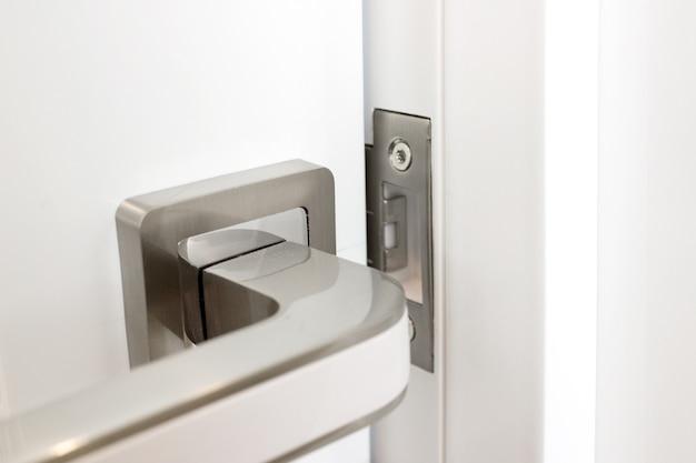Modern metal handle on white door close-up interior detail.