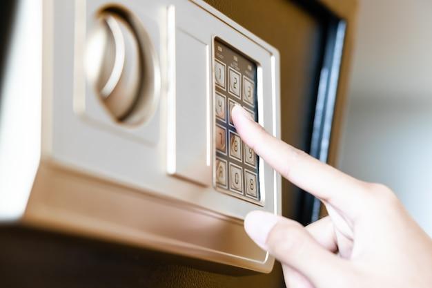 호텔 객실의 옷장 선반 안에 있는 현대적인 금속 금고, 객실 투숙객이 귀중품을 보관할 수 있는 보안 안전 전자 키패드 사물함에 손으로 누르는 암호