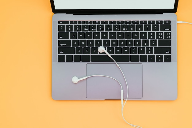 Современный металлический ноутбук и белые наушники, изолированные на оранжевой поверхности