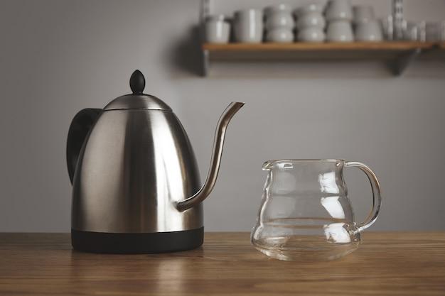 Teiera metallica moderna con pentola trasparente per caffè filtrato in un tavolo di legno spesso nella caffetteria