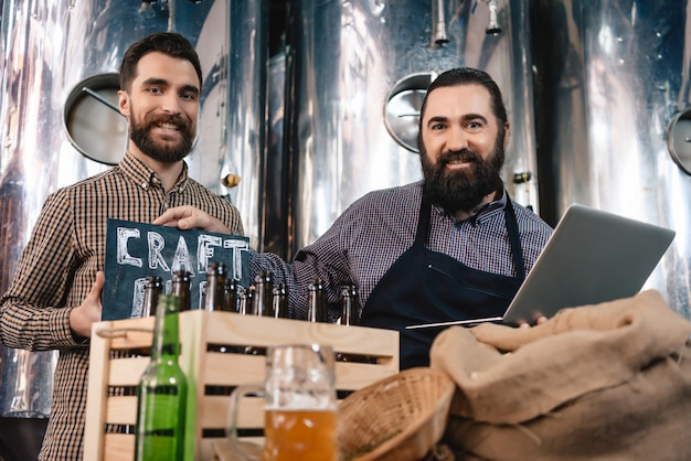 Modern microbrewery workers craft beer production.